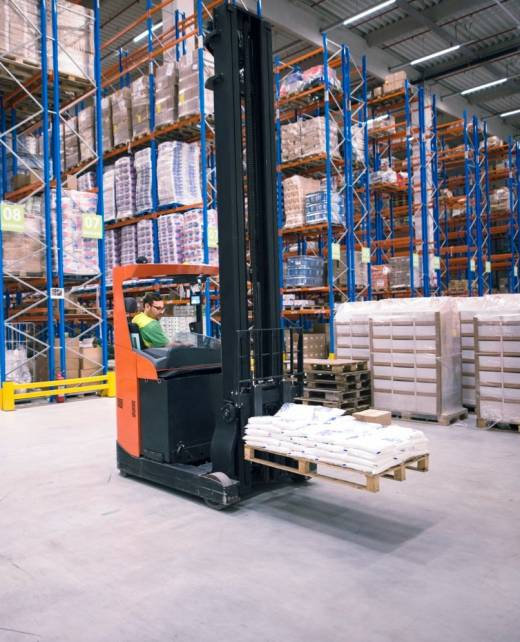 worker-operating-forklift-machine-relocating-goods-large-warehouse-center-min